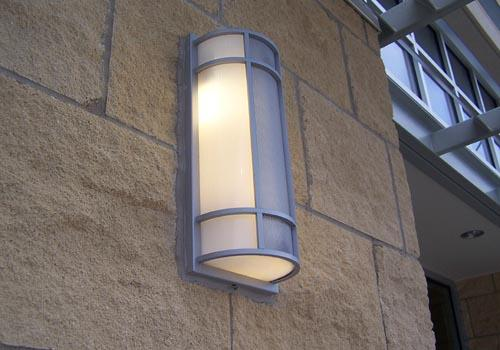 Hera Series illuminated & mounted against uneven surface sand textured brick wall with caulking.